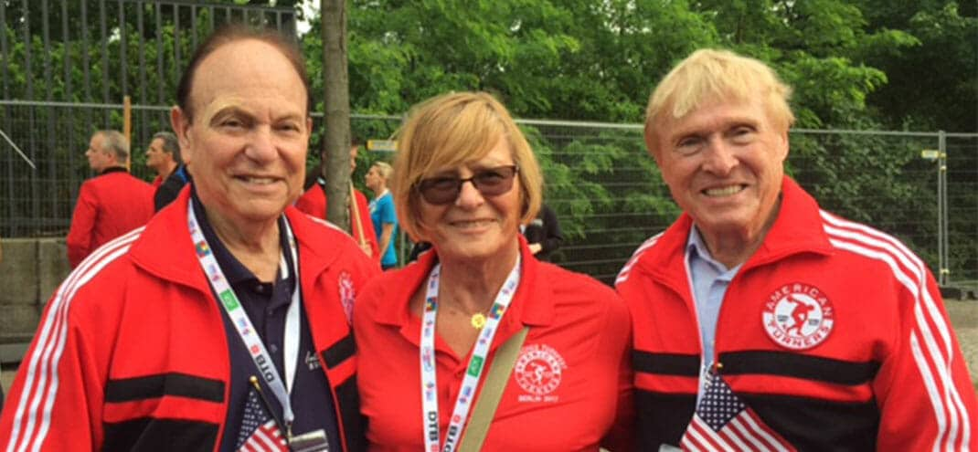 group of three gymnastics coaches holding small american flags