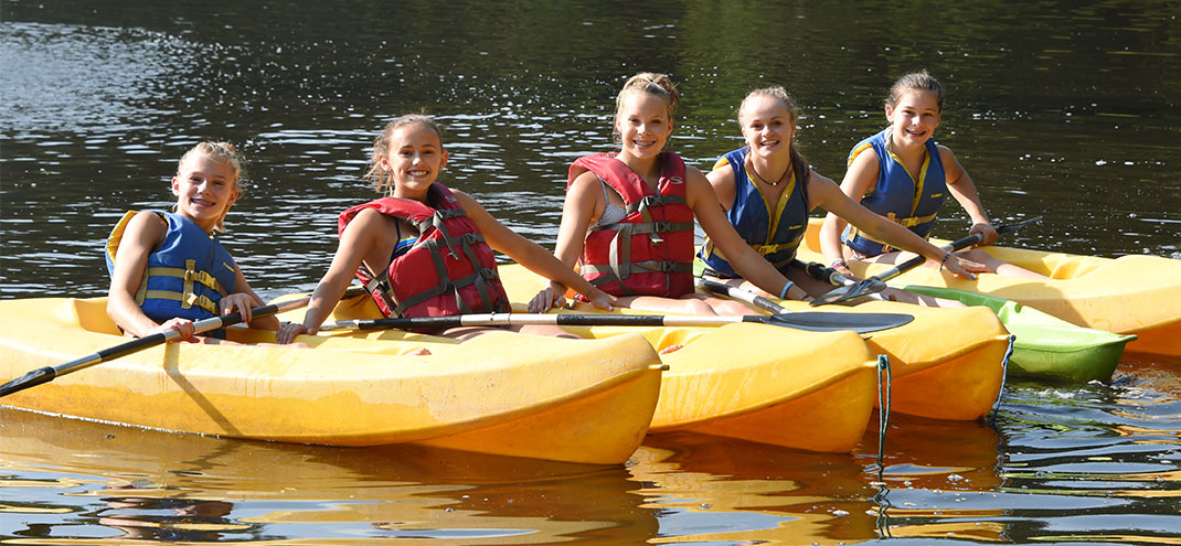 girls smiling in kayaks