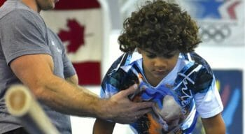 male gymnast teaching boy gymnast to use bars
