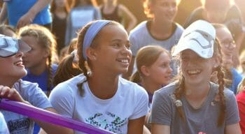 girls smiling and sitting on the bleachers