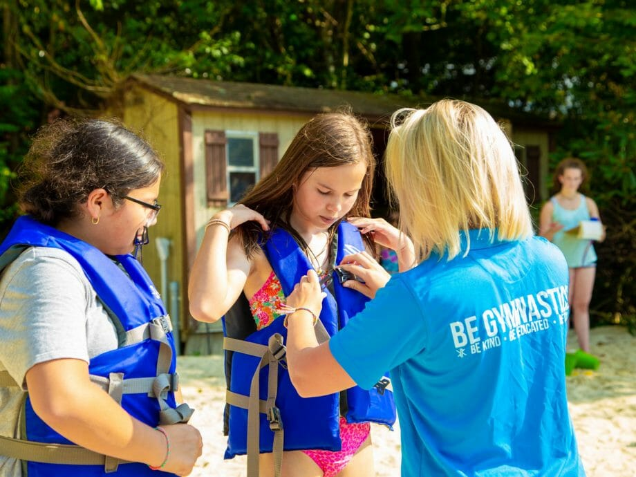 staff member helping campers put on life jackets