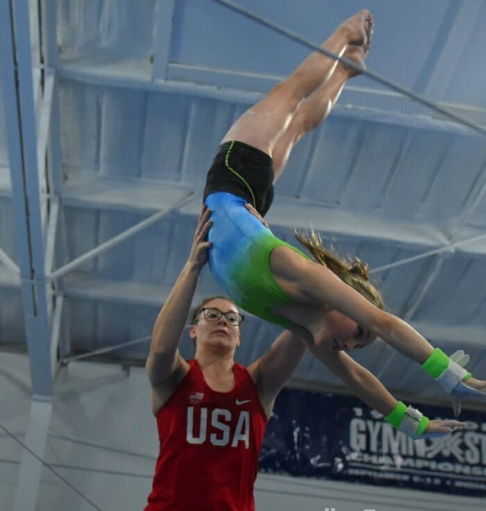 young female gymnast doing fly away with assistance from coach