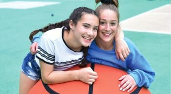 girls leaning on extra large inflatable basketball