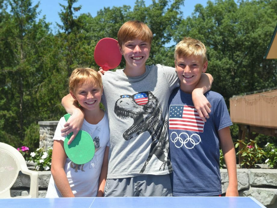 campers embracing holding pingpong paddles