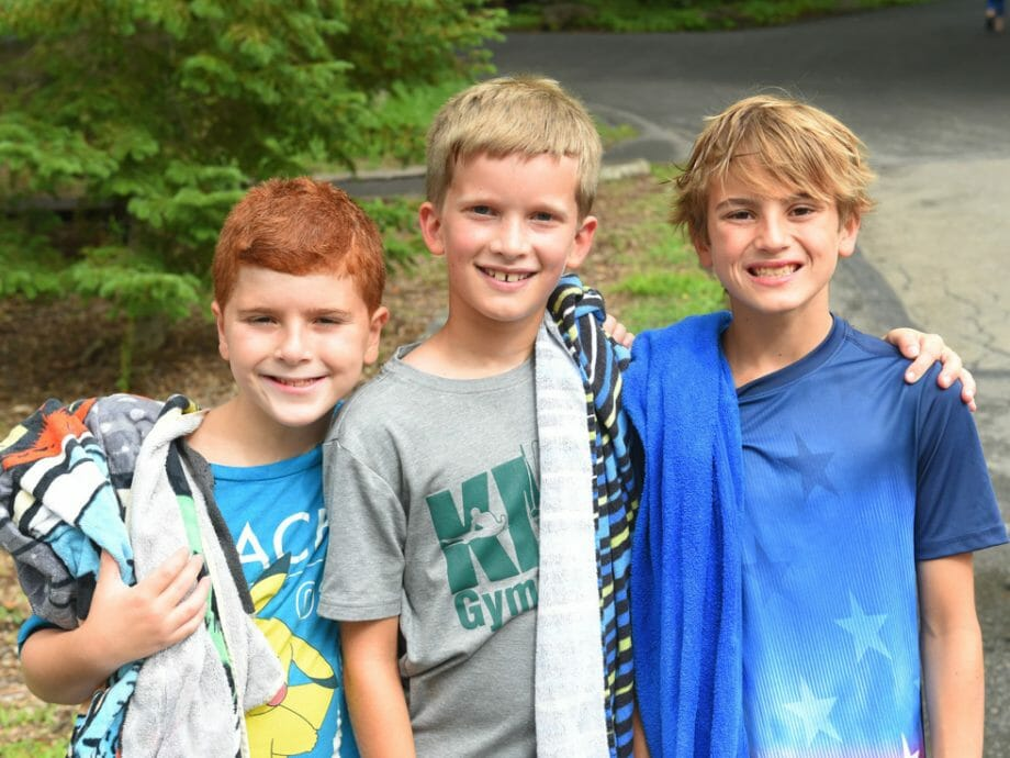 three boys with their towels before going swimming