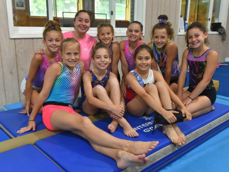 girls sitting on a mat in the beam gym