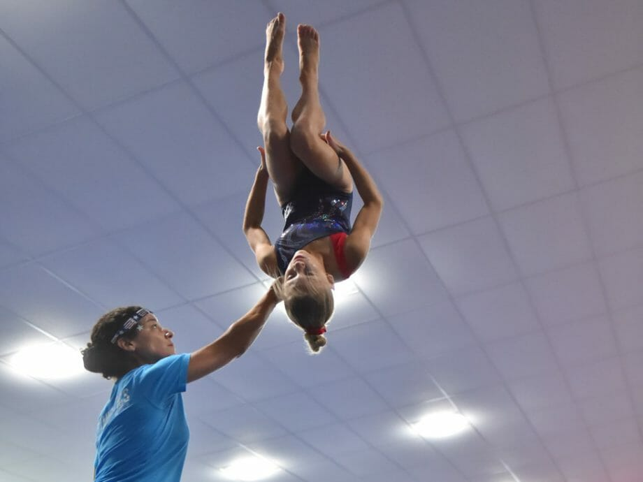 girl doing an aerial summersault with help from the instructor