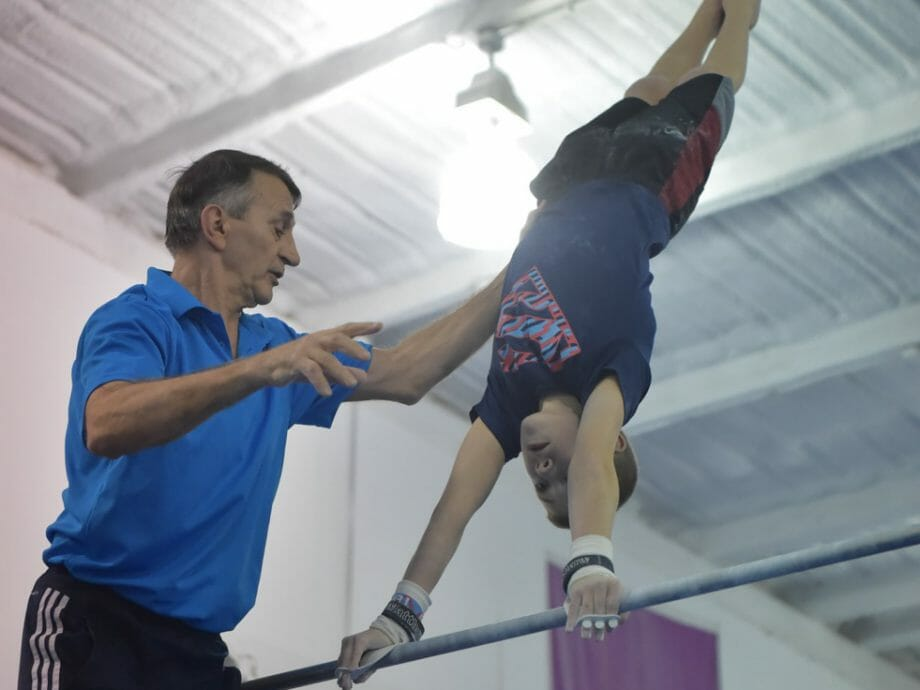 boy being instructed on the high bar
