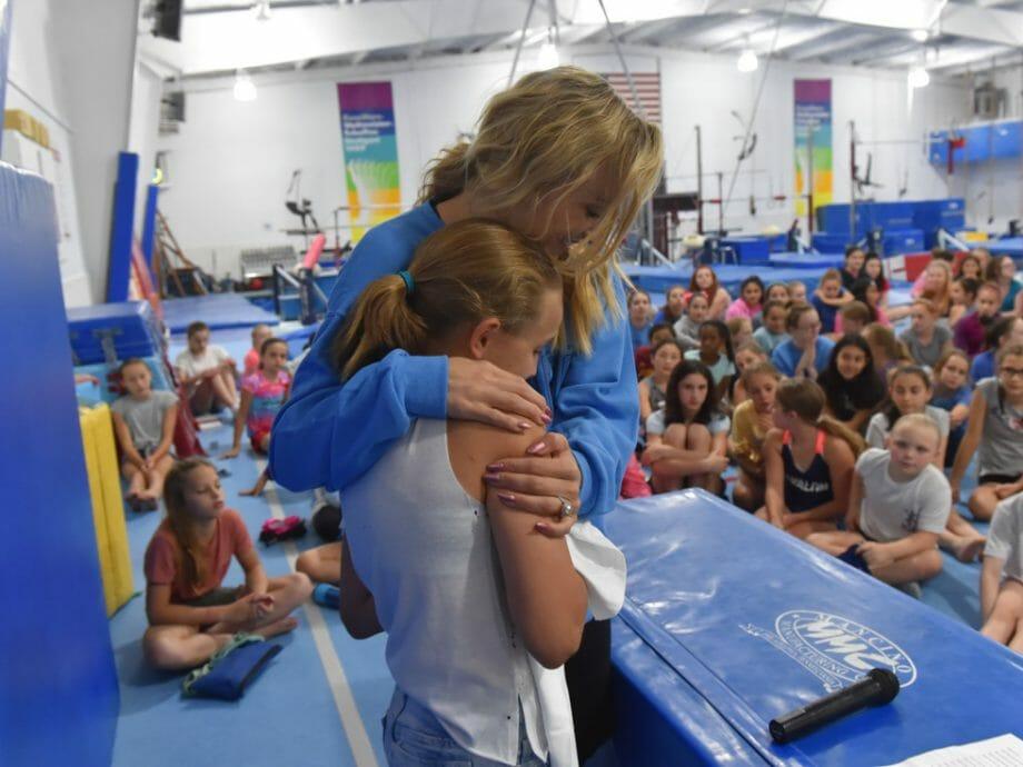 candid photo of Nastia Liukin hugging a camper