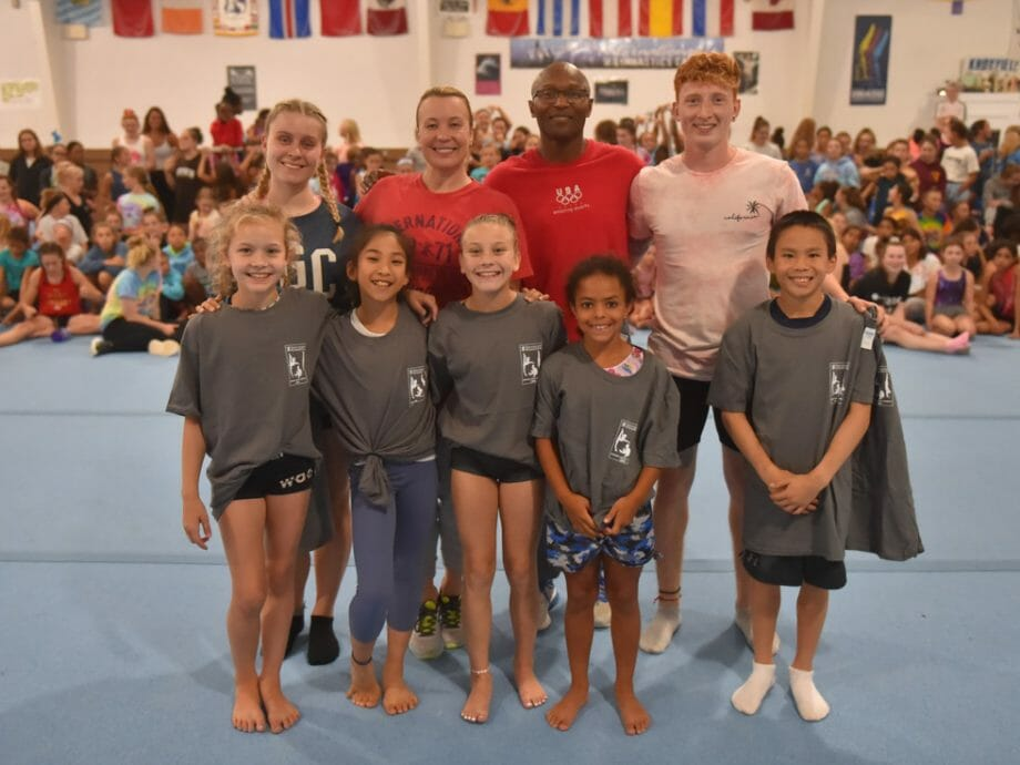 group of campers posing with their instructors in the olympic gym
