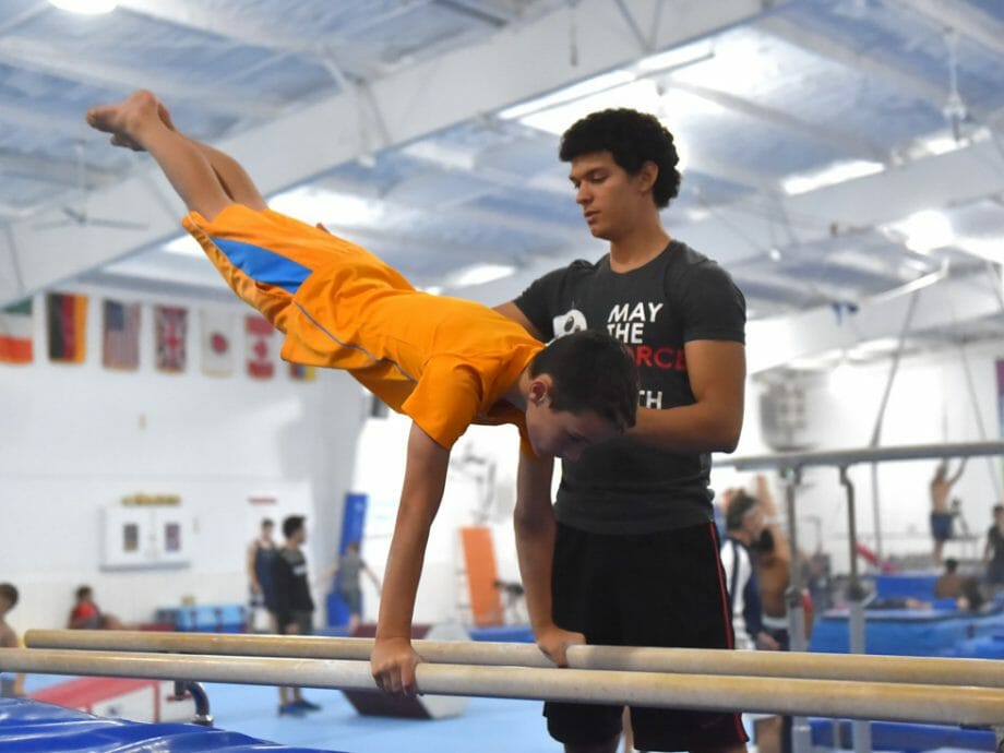 boy being instructed on the parallel bars