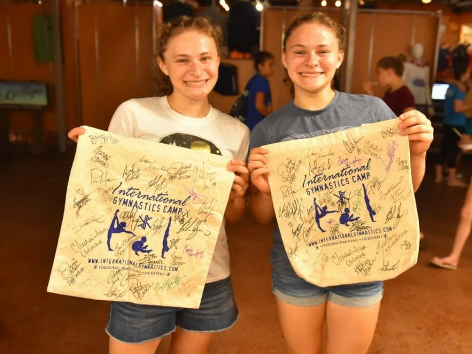 two campers holding their IGC pennants with signatures from celebrity guests