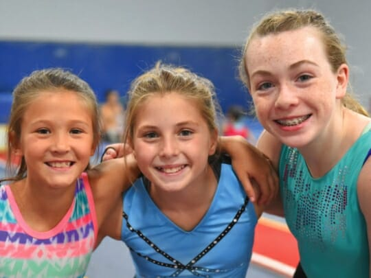 three girls with arms around each other at gymnastics camp