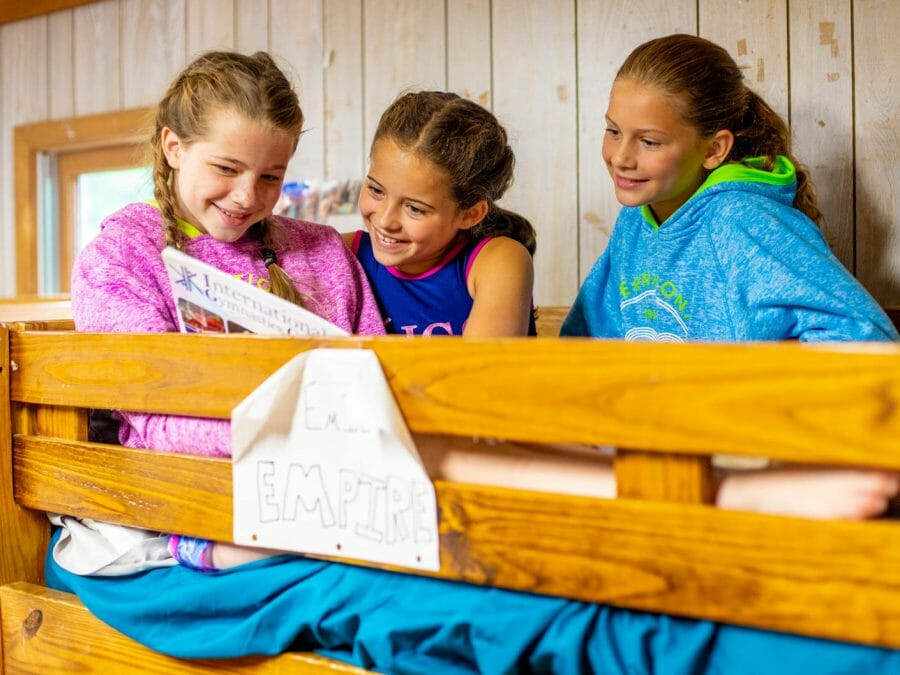 girls sitting atop one of the bunk beds in a cabin