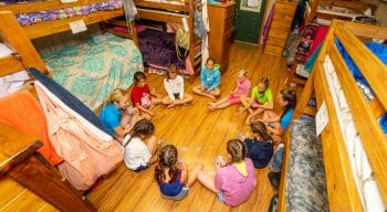 counselors and campers sitting in a circle on the floor of one of the cabins