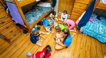 campers and counselors sitting in a circle on the floor of a cabin