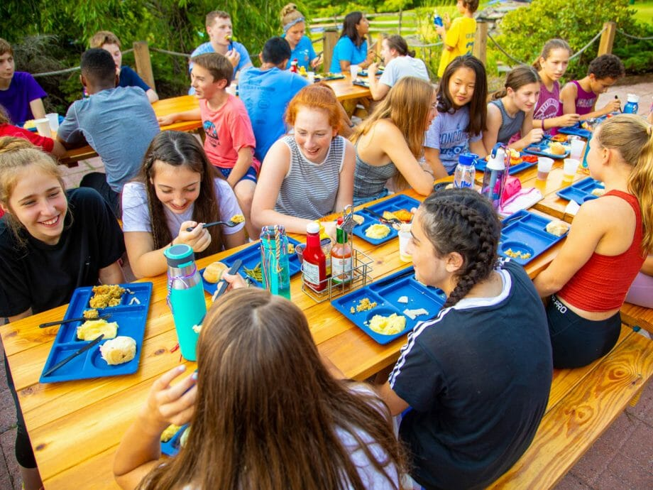 children laughing and eating at picnic tables