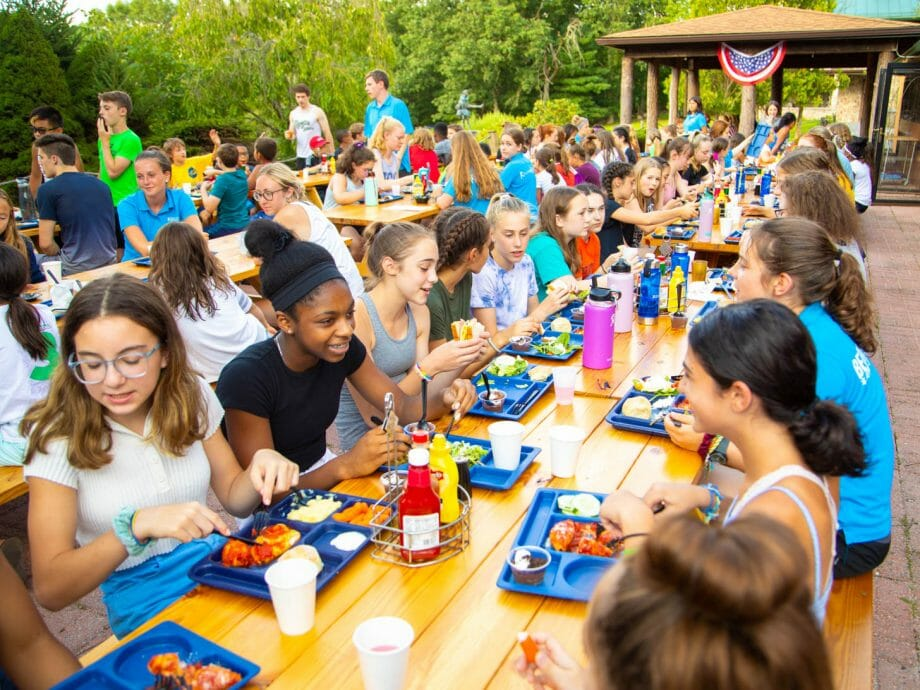 large group of kids and adults eating at picnic tables