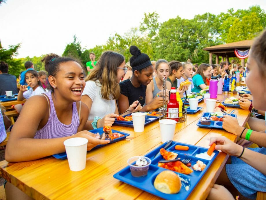 group of young girls eating at picnic tables