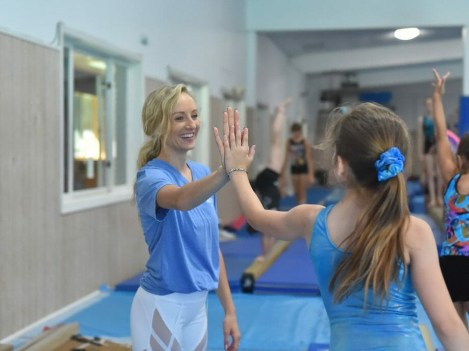 Nastia Liukin giving a high five to a camper