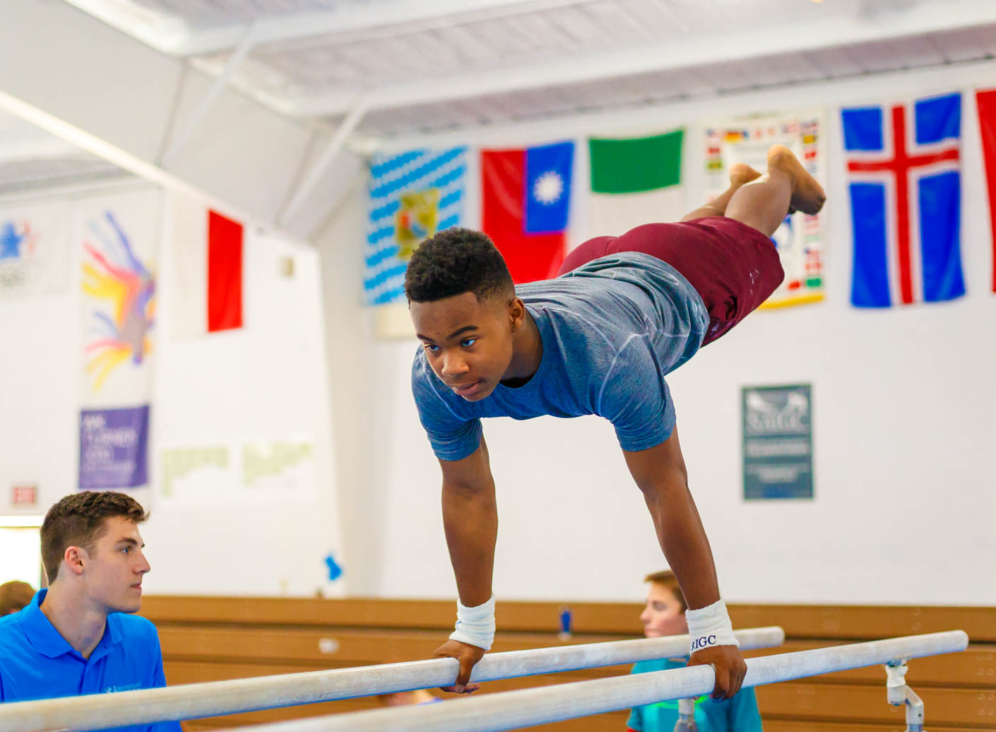 camper being coached on the parallel bars