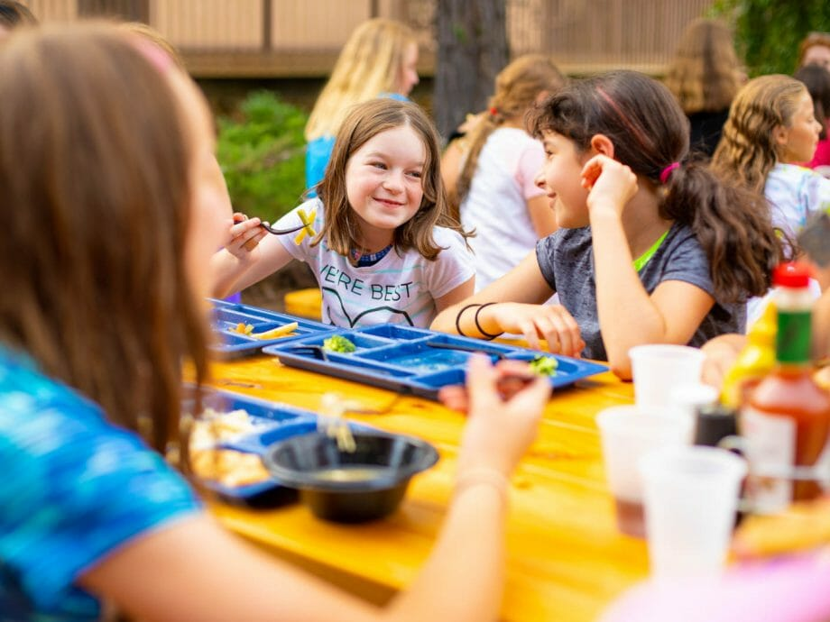 campers socializing while eating outside at picnic tables