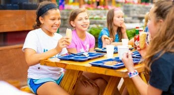 campers eating and socializing outside at the picnic tables