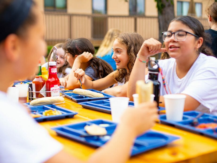campers eating at the outside picnic tables