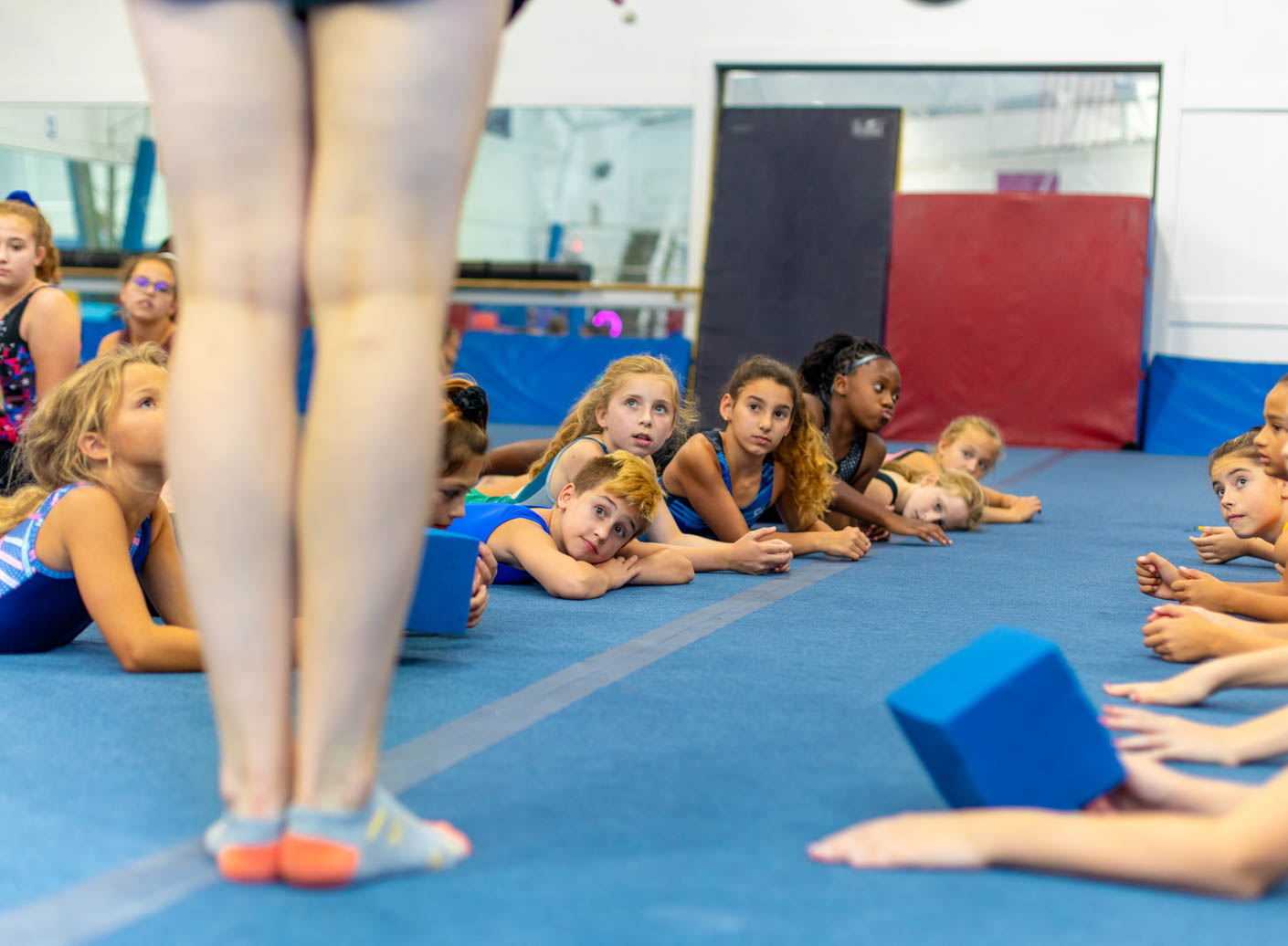campers looking on eagerly while sitting on the mats during instruction