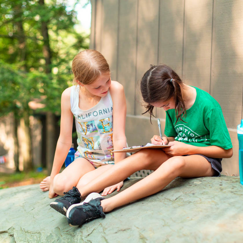 two campers sitting down writing on a clipboard