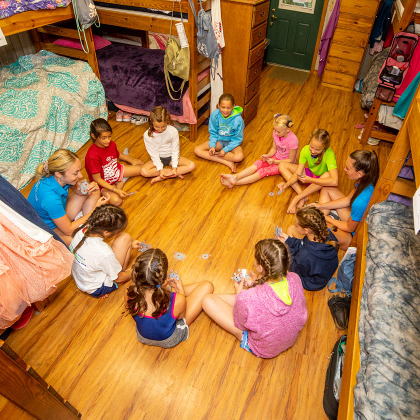 campers sitting in a circle in their cabin