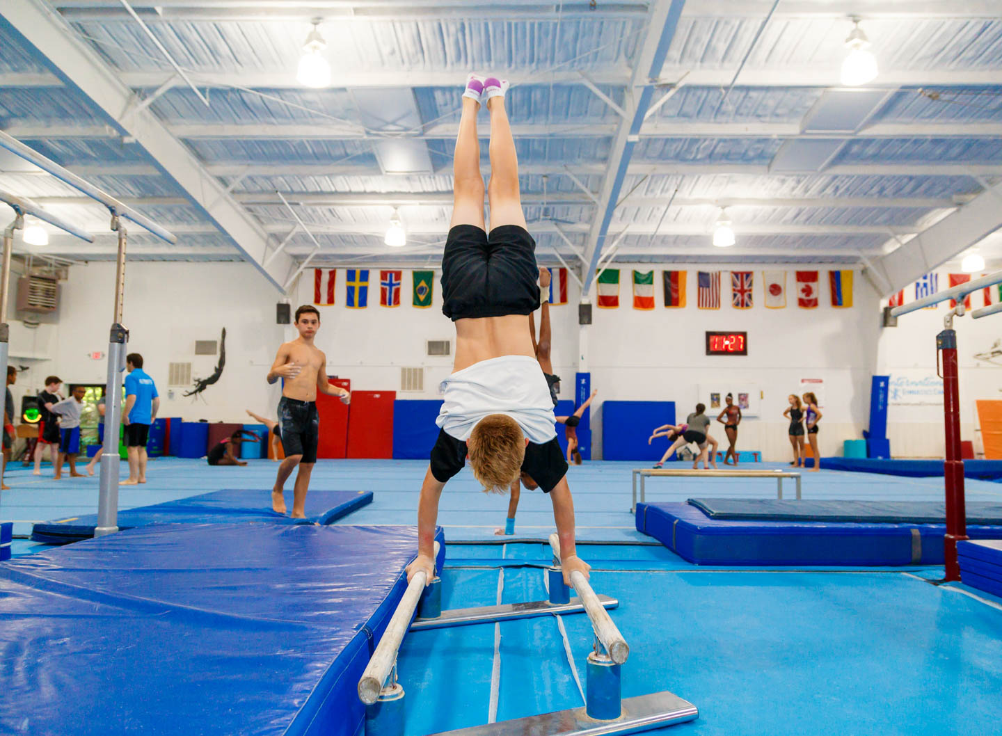 boy upside down on parallel bars