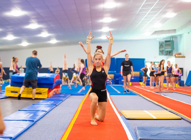 female gymnast training on a long run mat