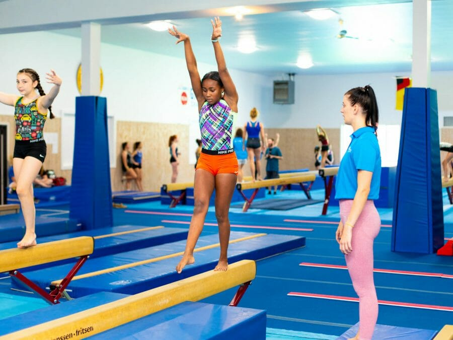 gymnasts being instructed on the balance beam