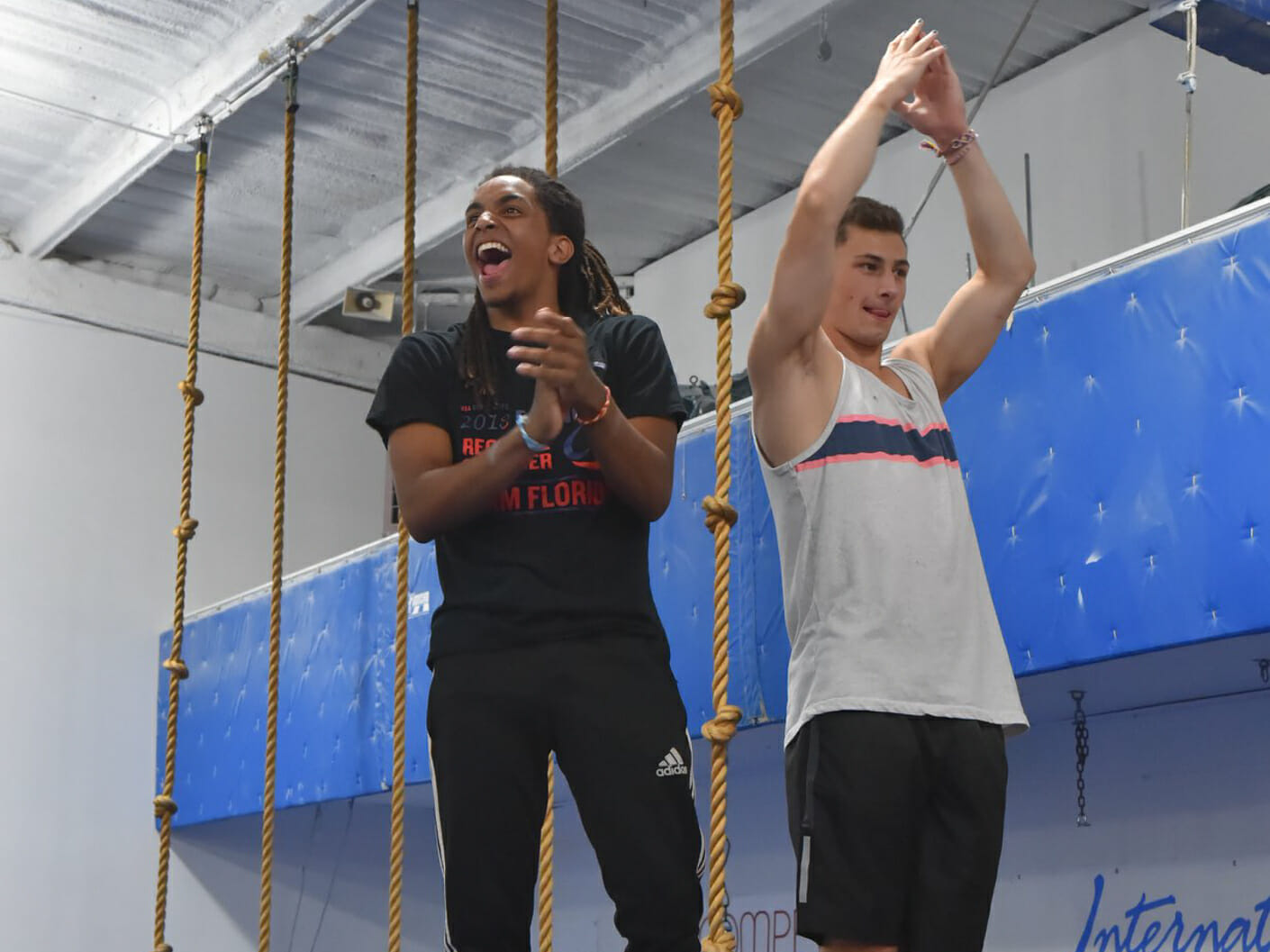 teen camper standing after a dismount with an instructor who's smiling
