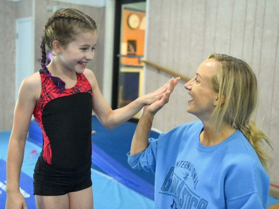 younger camper giving a high five to Nastia Liukin