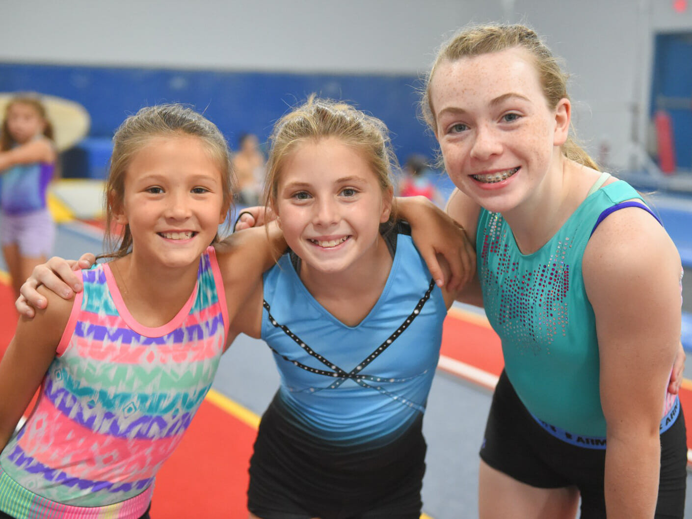 three campers embracing for a photo in the olympic gym