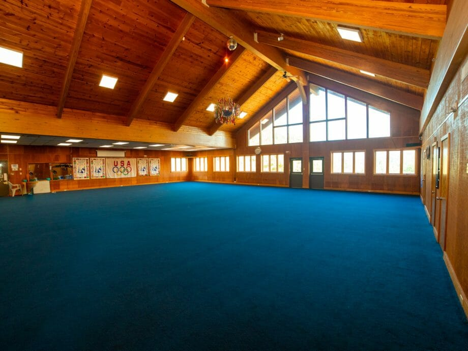 the wide open floor gym with log cabin style ceiling
