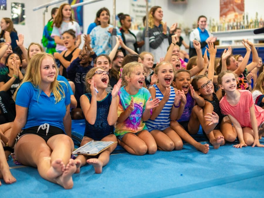girls sitting on the mat, cheering