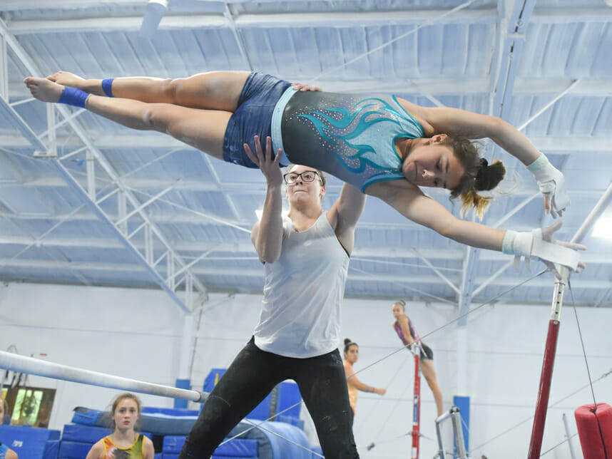 camper being instructed by an instructor on the uneven bars