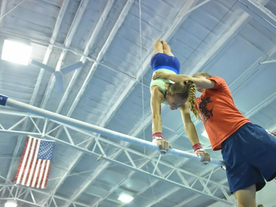 camper being instructed on the uneven bars