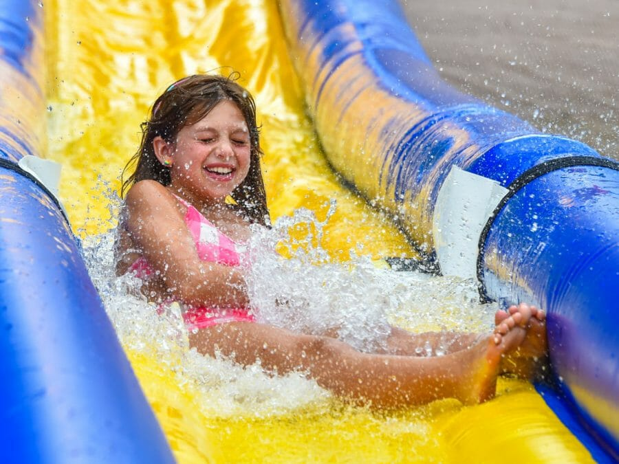 younger camper sliding down the water slide