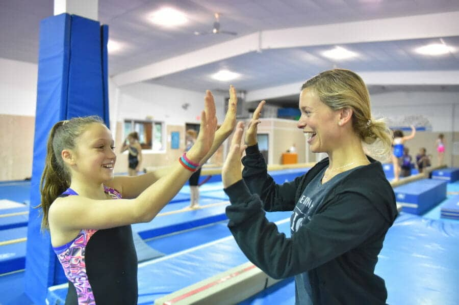coach and gymnast high fiving
