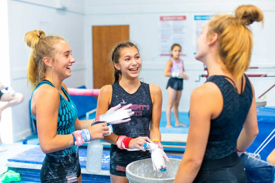 female gymnasts putting powder on hands