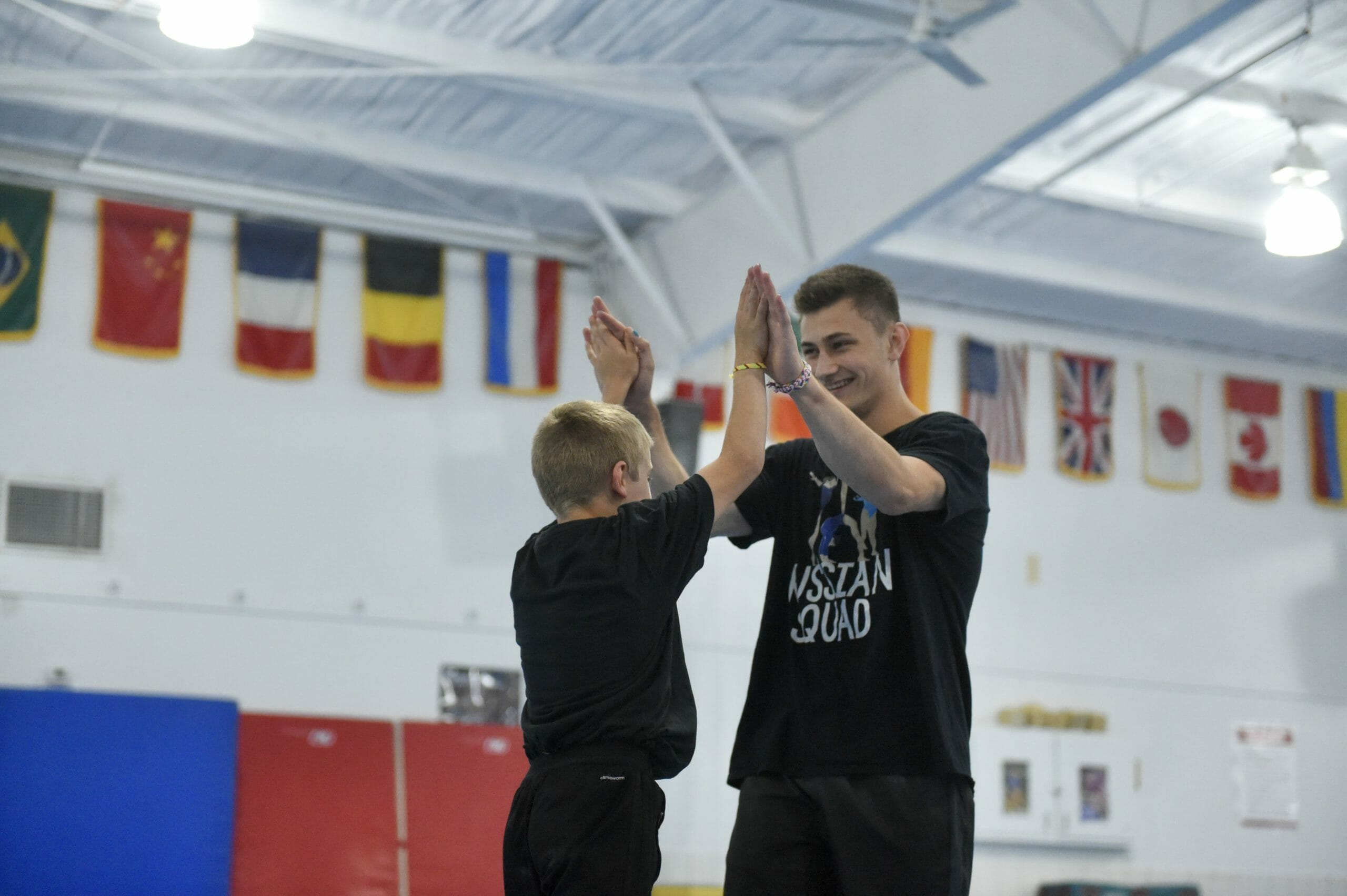 young male gymnast high fiving coach