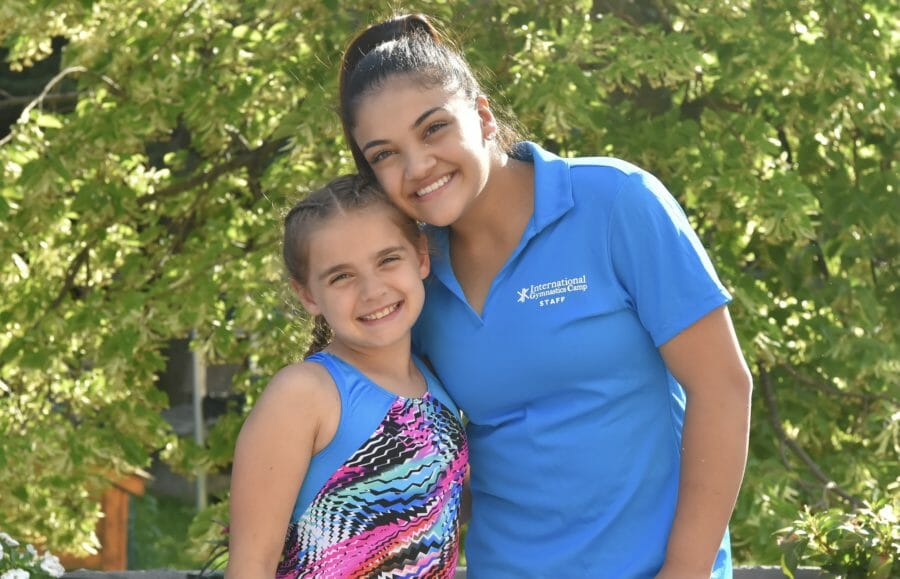 Celebrity gymnast with young girl, smiling