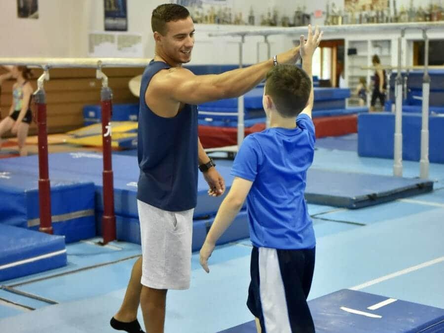 coach high-fiving young boy