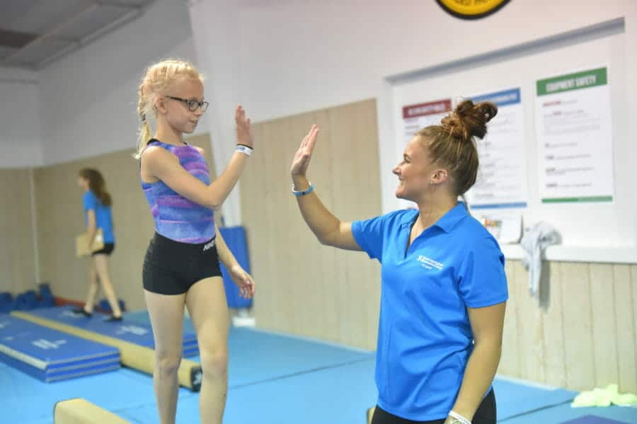 Coach high-fiving young girl standing on beam