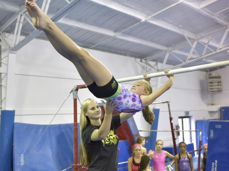 Coach helping young girl on the bar