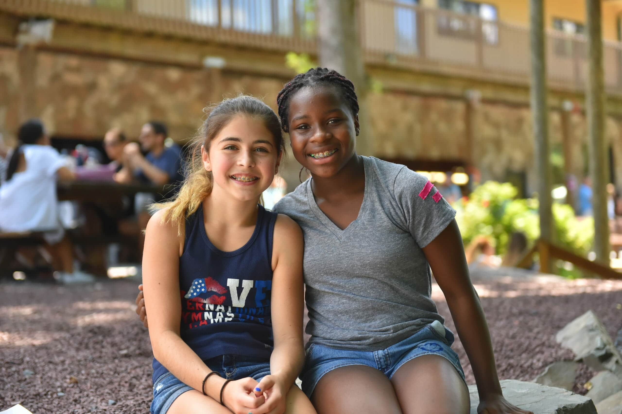two young female gymnasts smiling at camp